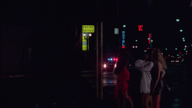 medium angle of prostitutes on sidewalk of hollywood boulevard. camera pans right to left as police car drives by with flashing lights or bizbar. city street. car pulls up to curb. man gets out and walks across street. - 売春者点の映像素材/bロール