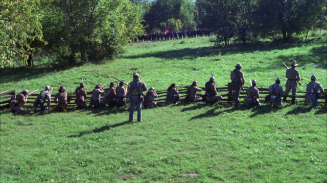 high angle down from behind line of confederate civil war soldiers. men shooting rifles form behind wood fence. woods or battlefield in bg. smoke rises. stunts. - confederate states of america stock videos & royalty-free footage