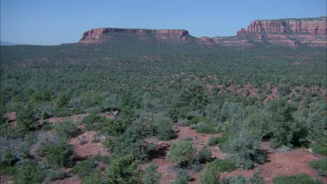 aerial tracking shot of two men walking injured or limping through desert. - arizona stock-videos und b-roll-filmmaterial