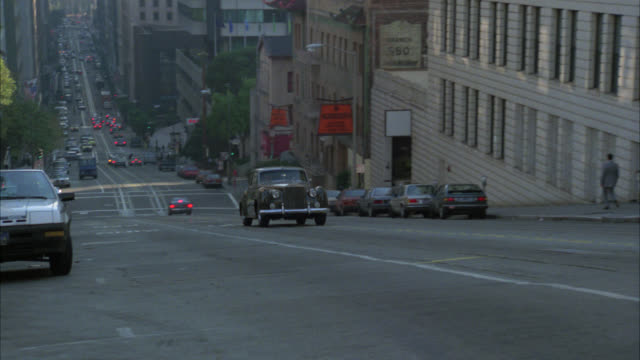 pan left to right of car or rolls royce driving up hill on city street. apartment buildings in residential area. nob hill. american flag on top of high rise building, mark hopkins hotel. could be government building. vintage car. - rolls royce stock videos and b-roll footage