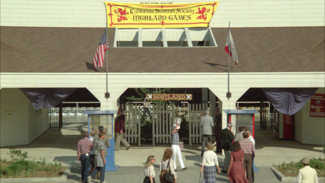 "pull back from sign above entrance to a building that reads ""the california scottish society highland game"" to show people walking through parking lot in front of building. scottish kilts. - game show stock videos and b-roll footage"