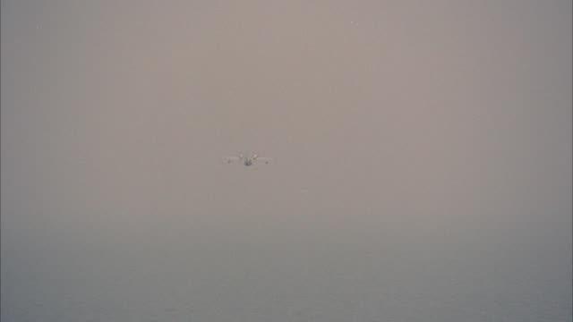pan right to left of a grumman goose seaplane, pontoon or airplane flying low over ocean. cliffs, rocks in fg. os 28-1. coastline. - 水上飛行機点の映像素材/bロール