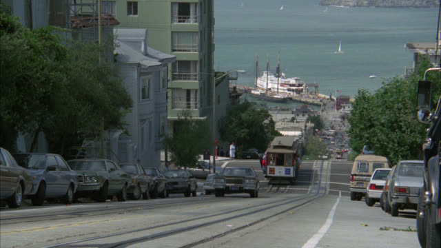 vídeos de stock, filmes e b-roll de pan right to left from city street on hill, ocean or bay bg.  apartment. do not use if actor is recognizable. r685-5 is better shot. cable car or trolley. residential area. - cable