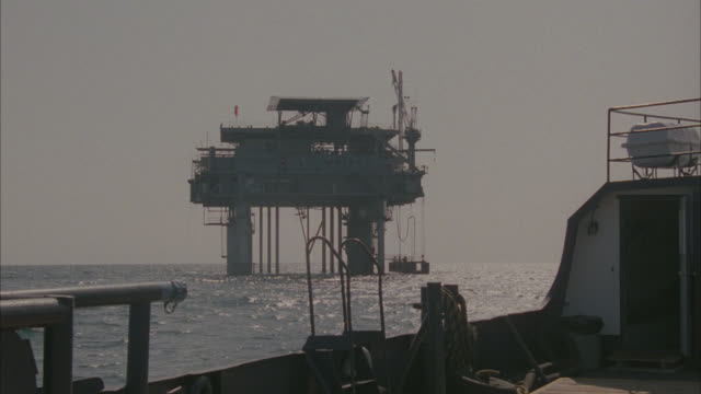 wide angle of oil rig in ocean from oil tanker with deck railing in fg.  off-shore oil drilling platform. - oil rig boat stock videos & royalty-free footage