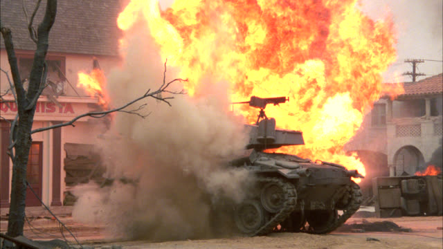 WIDE ANGLE OF MILITARY TANK IN MIDDLE OF DEMOLISHED SMALL TOWN, COULD BE WWII, WORLD WAR II, EUROPEAN VILLAGE. TANK EXPLODES AND A FIREBALL, FLAMES, FIRE SMOKE AND DEBRIS FLY INTO THE AIR.  EXPLOSIONS.