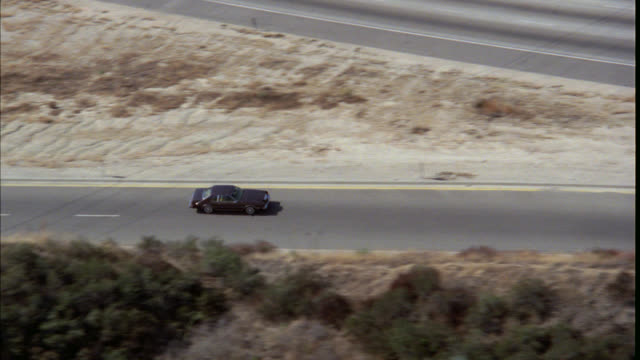 AERIAL TRACKING SHOT OF 1970'S BROWN TWO DOOR CAR DRIVING DOWN SUBURBAN STREETS THROUGH COMMERCIAL AREA STORES SHOPS PARKING LOTS. SEE TREES, INTERSECTIONS, GAS STATIONS. CAR TURNS RIGHT ON TO FREEWAY ON RAMP AND MERGES ONTO FREEWAY OR HIGHWAY.
