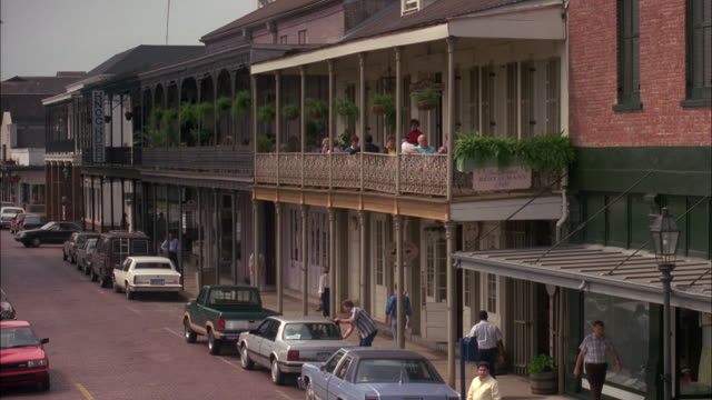 wide angle of new orleans louisiana street with two story buildings, shops, restaurants, people sitting on balcony of second story and people walking on sidewalk. french quarter. downtown. - new orleans stock videos & royalty-free footage