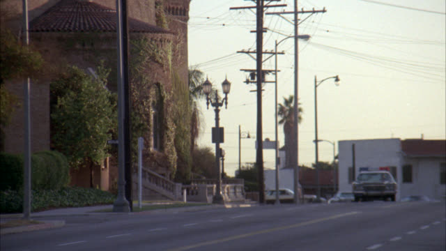 wide angle of black and white police car driving past large brick church. blue vw volkswagen car follows behind police car. police car swerves. - volkswagen stock-videos und b-roll-filmmaterial