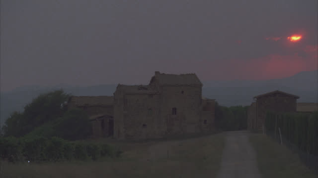 wide angle of rustic two story stone country house in countryside or rural area. could be farmhouse. sun setting over hills in bg. road. tall trees or shrubs line dirt road. - masseria video stock e b–roll