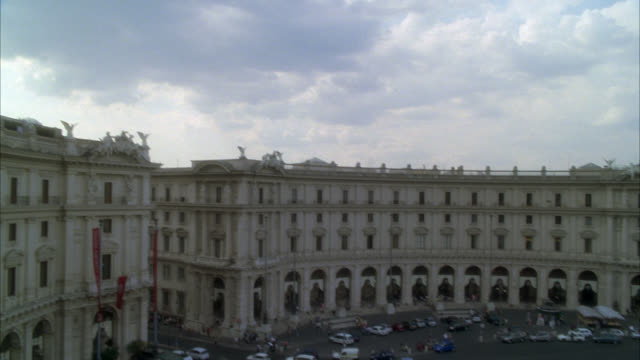pan down of piazza della repubblica and statues in fountain of the naiads in roundabout or traffic circle. cars and buses driving on city streets. people or pedestrians. three-story stone building, could be government office building or museum. europe. - piazza video stock e b–roll