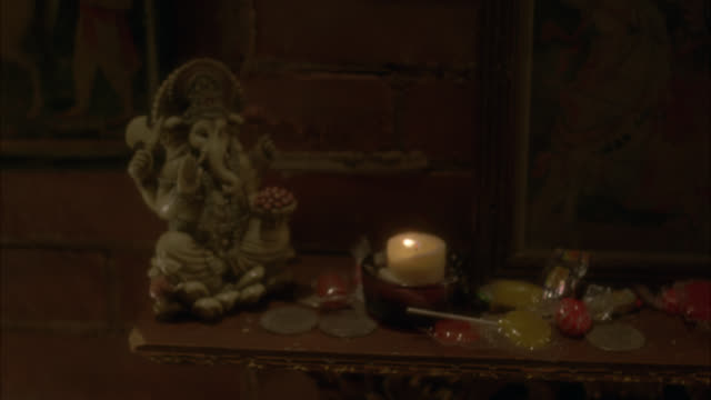stockvideo's en b-roll-footage met close angle of statue of hindu god, candle, coins, money and candy. could be altar. lollipops. - altaar