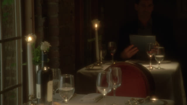 medium angle of table for two in upper class romantic restaurant. candle. wine bottle and glasses. man in bg. - 名声点の映像素材/bロール