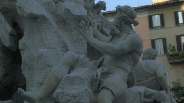 pan up of the fountain of the four rivers in piazza navona. stone statues or sculptures. obelisk. - piazza navona stock videos & royalty-free footage