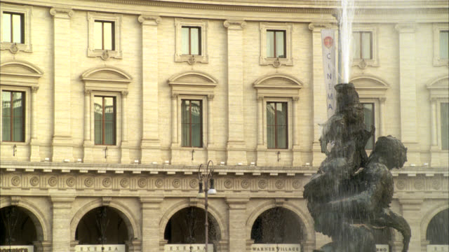 close angle of water spraying on statue in fountain of the naiads in piazza della repubblica. three-story upper class stone building, could be hotel, government office building or museum. europe. - piazza video stock e b–roll