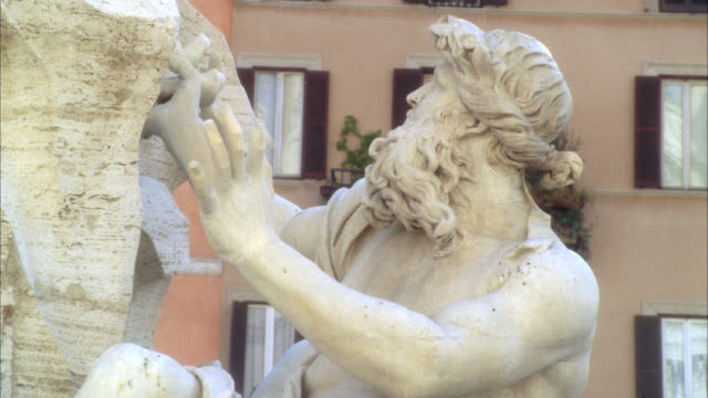 pan left to right of stone sculpture or statue on fountain of the four rivers in piazza navona. pan up to catholic basilica church of sant'agnese of agone. - piazza navona stock videos & royalty-free footage
