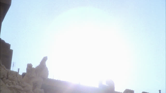 pan up to sun over stone sculpture or statue on fountain of the four rivers in piazza navona. - piazza navona stock videos & royalty-free footage