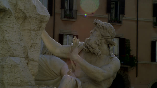 pan up to stone sculpture or statue on fountain of the four rivers in piazza navona. sunlight and halation - piazza navona stock videos & royalty-free footage