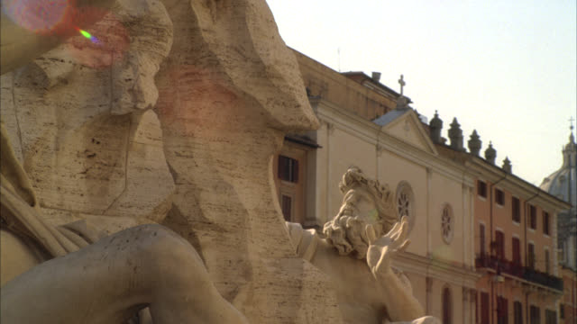 pan left to right of stone sculpture or statue on fountain of the four rivers in piazza navona. multi-story middle class apartment buildings in bg. - piazza navona stock videos & royalty-free footage