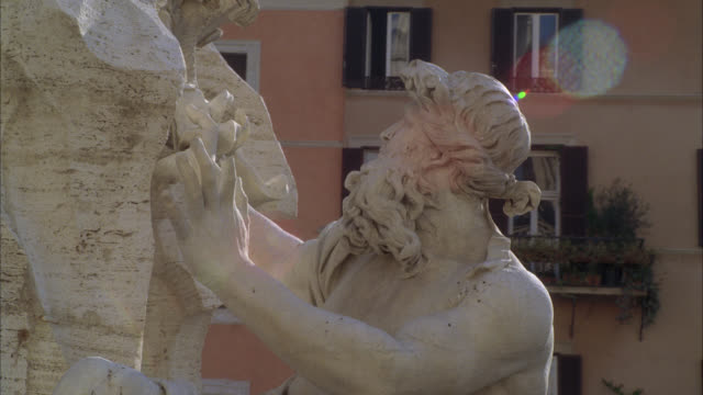 pan right to left of stone sculpture or statue on fountain of the four rivers in piazza navona. multi-story middle class apartment buildings in bg. - piazza navona stock videos & royalty-free footage