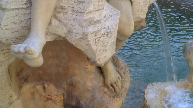 close angle of feet of stone sculpture or statue on fountain of the four rivers in piazza navona. water flowing down. - piazza navona stock videos & royalty-free footage