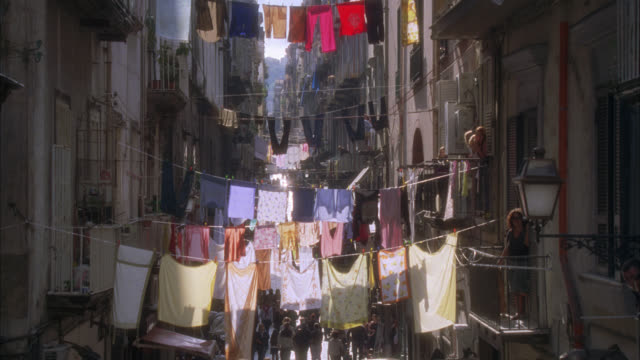 pan up of laundry on clotheslines across city street or alley. people or pedestrians walking. could be naples. apartment buildings and balconies. - alley stock videos & royalty-free footage