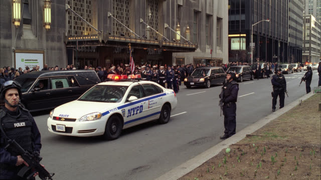 WIDE ANGLE OF PARADE OR MILITARY FUNERAL PROCESSION WITH ARMED POLICE OFFICERS CONTROLLING CROWD ON SIDEWALK AS BAGPIPERS MARCH DOWN STREET. FLAGS. WALDORF ASTORIA HOTEL IN BG. POLICE CARS WITH FLASHING LIGHTS OR BIZBAR FOLLOW. HEARSE VISIBLE.