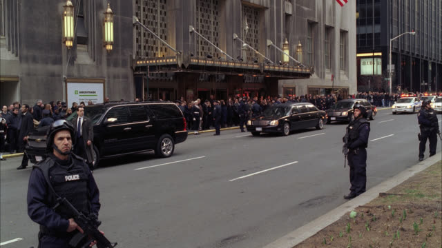 wide angle of parade or military funeral procession with armed police officers controlling crowd on sidewalk. waldorf astoria hotel in bg. police cars with flashing lights or bizbar follow. limousines. - ウォルドルフ・アストリア点の映像素材/bロール