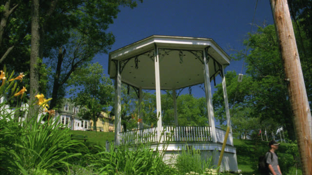 stockvideo's en b-roll-footage met up angle of gazebo with park and middle class, two story houses on hill in bg. plants, flowers in fg. residential area or neighborhood. - gazebo