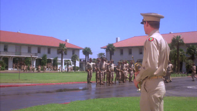 PAN UP OF ARMY OR MILITARY SOLDIERS LINING UP AND STANDING AT ATTENTION IN FORMATION. MARCHING TROOPS. ARMY BASE. SCHOFIELD BARRACKS. SOLDIER PLAYS BUGLE IN COURTYARD LAWN TROPICAL WITH PALM TREES.