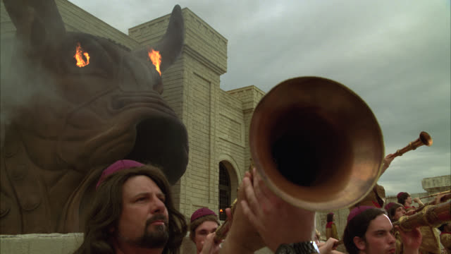 vídeos de stock, filmes e b-roll de close angle of pagan temple with bull's head sculpture covering entrance. flames and smoke inside bull's head. brick building. trumpeters or horn players outside of temple. men hold up horns. - músico