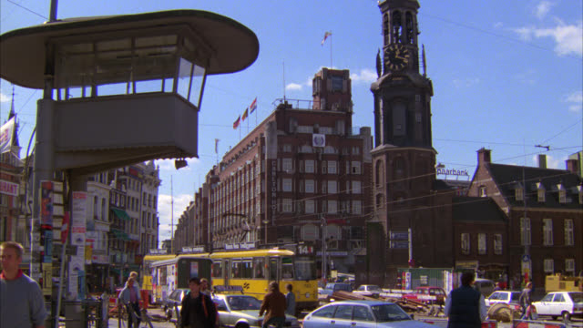 wide angle of busy european city street. streetcars or trolleys. multi-story brick office or apartment buildings. people or pedestrians walking. munttoren or mint tower, clock tower in muntplein square. - アムステルダム点の映像素材/bロール