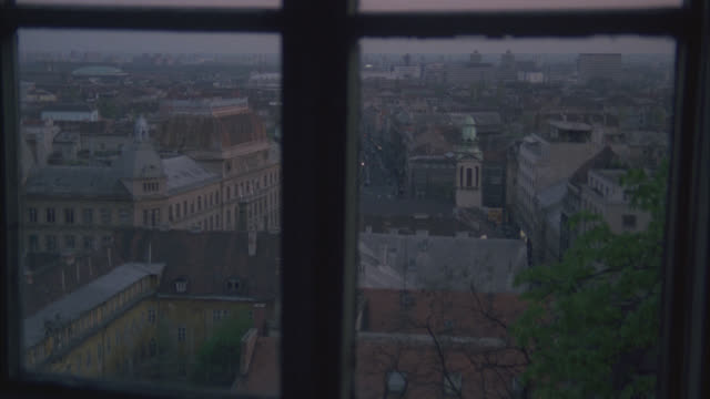 """high angle down from window of city skyline and buildings below. sign on building reads """"medimurska."""" bricks buildings. could be apartment buildings. could pass for any eastern europe city. tower with with green dome and steeple in fg. dusk. - steeple stock videos & royalty-free footage"""