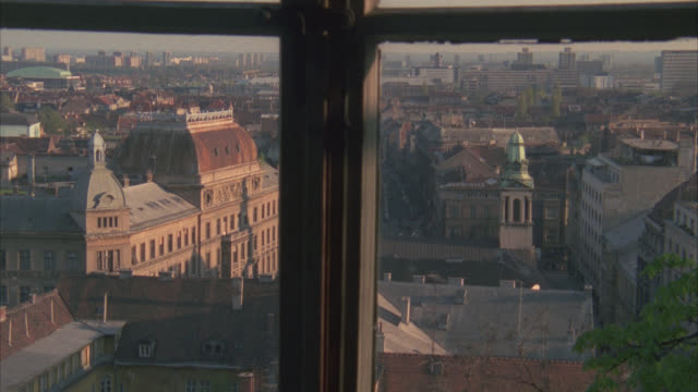 """high angle down from window of city skyline and buildings below. sign on building reads """"medimurska."""" bricks buildings. could be apartment buildings. could pass for any eastern europe city. tower with with green dome and steeple in fg. - steeple stock videos & royalty-free footage"""