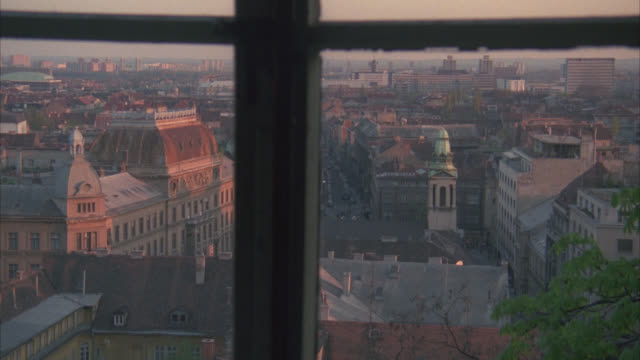 """high angle down from window of city skyline and buildings below. sign on building reads """"medimurska."""" bricks buildings. could be apartment buildings. could pass for any eastern europe city. tower with with green dome and steeple in fg. sunset. - steeple stock videos & royalty-free footage"""