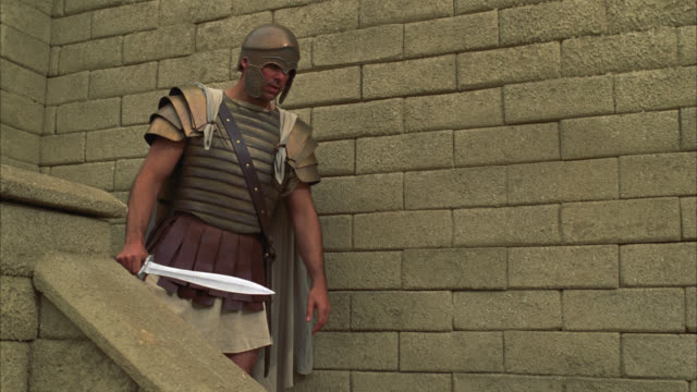 medium angle of soldier in with ancient helmet and swords. man defends stone stairs from men in togas with clubs. biblical times. - weaponry stock videos & royalty-free footage