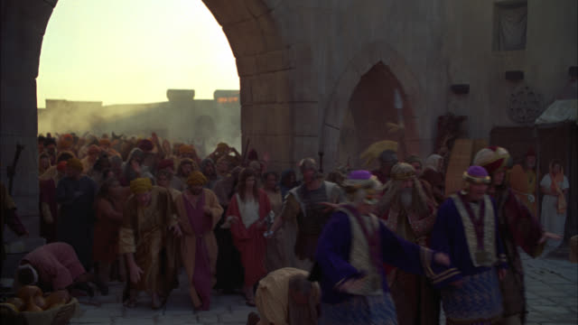 medium angle of mob or crowd running through street. stone arch in bg. people wear robes. could be riot or panicking crowd. roman soldiers amongst crowd. - roman stock videos and b-roll footage