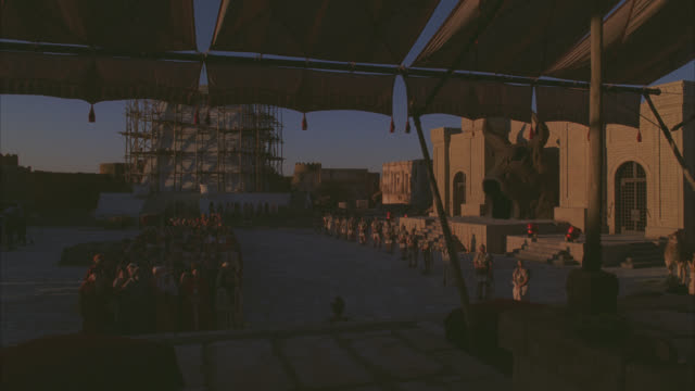 wide angle of crowd of townspeople cheering with hands in air in town square. - biblical event stock videos & royalty-free footage