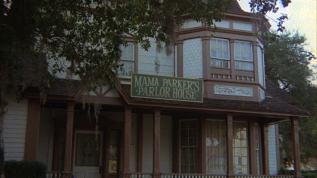 stockvideo's en b-roll-footage met zoom in on sign for mama parker's parlor house, two story victorian house with porch in suburb or residential area. - victoriaanse stijl