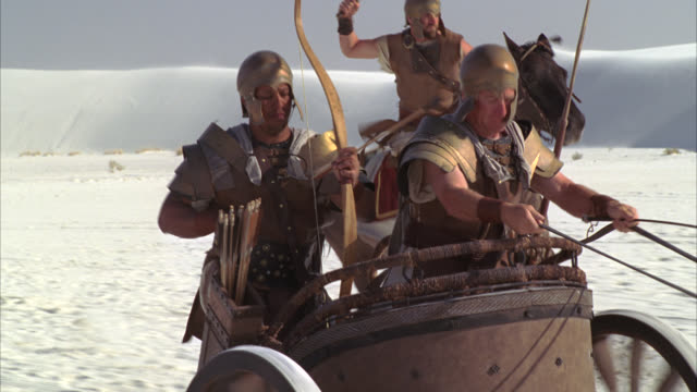 tracking shot of two roman soldiers in a horse-drawn chariot. one is an archer, shooting arrows. third soldier in bg riding horse. could be attack, battle or war. desert sand dunes. could be white sands new mexico. - roman soldier stock videos and b-roll footage