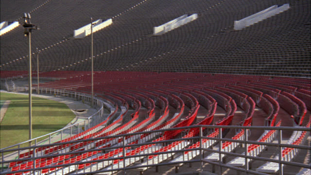 PAN RIGHT TO LEFT OF EMPTY ROSE BOWL STADIUM TO PRESS BOX. FOOTBALL FIELD. SPORTS. BLEACHERS, STANDS.