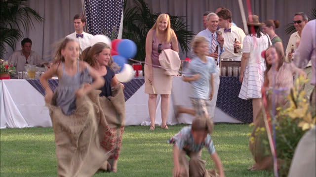 wide angle of children having potato sack race. could be upper class celebration. could be easter or fourth of july. - sack race stock videos & royalty-free footage