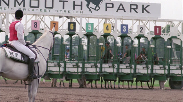 pan left to right from jockeys on horses racing out of the starting gate and around racetrack. monmouth park, oceanport, new jersey. - horse racing stock videos & royalty-free footage