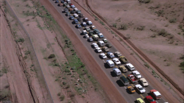 AERIAL OVER TRAFFIC JAM ON DESERT HIGHWAY BELOW JAM DESERT MILITARY TRUCKS ON SIDE OF ROAD WITH CONVOY. COULD BE ACCIDENT OR DISASTER EVACUATION.