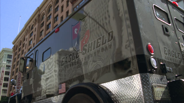 TRACKING SHOT OF ARMORED TRUCK DRIVING THROUGH DOWNTOWN CITY STREETS. MULTI-STORY OR HIGH RISE BRICK OFFICE OR APARTMENT BUILDINGS.