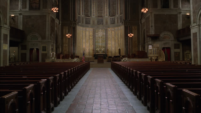 wide angle of interior of st. bartholomew's episcopalian church in new york city. american flag  at altar. lights go dim. - altare video stock e b–roll