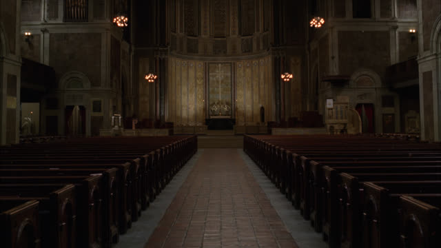 wide angle of interior of st. bartholomew's episcopalian church in new york city. altar and pews visible. lights dim. - altare video stock e b–roll