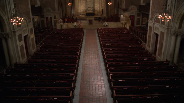 high angle down of interior of st. bartholomew's episcopalian church in new york city. american flag  at altar. lights go dim. - altare video stock e b–roll