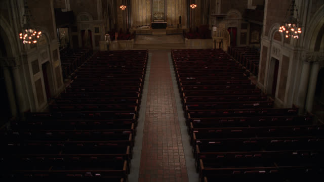 high angle down of interior of st. bartholomew's episcopalian church in new york city. altar and pews visible. lights dim. - altare video stock e b–roll