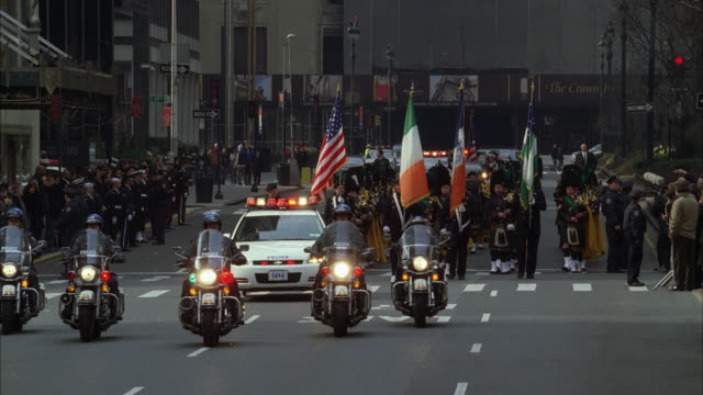 wide angle of military funeral in new york city. waldorf astoria hotel in bg. crowds gather on sidewalk near reporters. police motorcycle motorcade escorts hearse. bagpipers with flags. police officers and soldiers stand at attention on street. - funeral procession stock videos & royalty-free footage