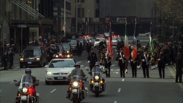 wide angle of military funeral in new york city. waldorf astoria hotel in bg. crowds gather on sidewalk near reporters. police motorcycle motorcade escorts hearse. bagpipers with flags. police officers and soldiers stand at attention on street. - ウォルドルフ・アストリア点の映像素材/bロール